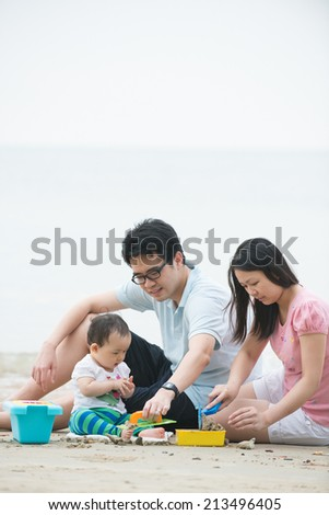 asian family playing on a beach during sunset - stock photo