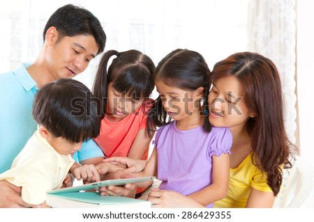 Asian family playing tablet computer