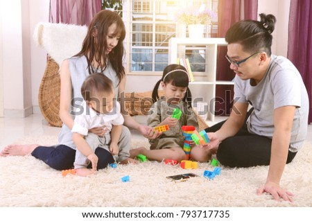 Asian family playing toys at living room