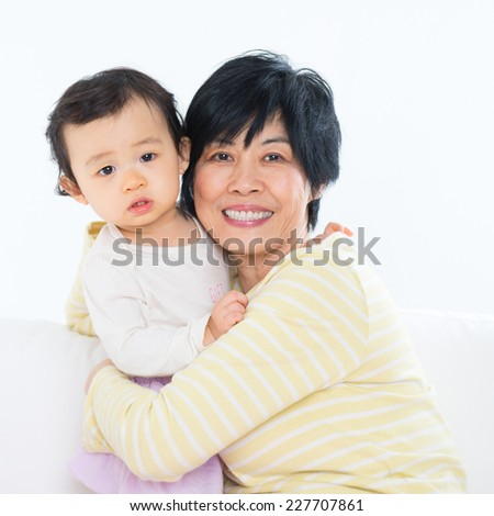 Asian family portrait, grandma and grandchild indoor living lifestyle at home. - stock photo