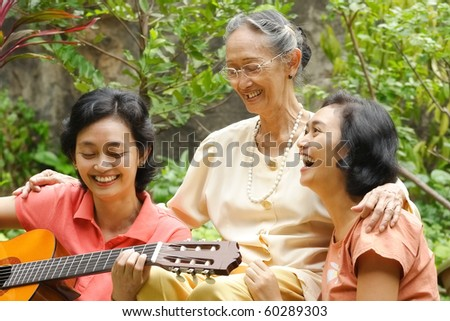 Asian family portrait of old mother relaxing together with her daughter at home - stock photo