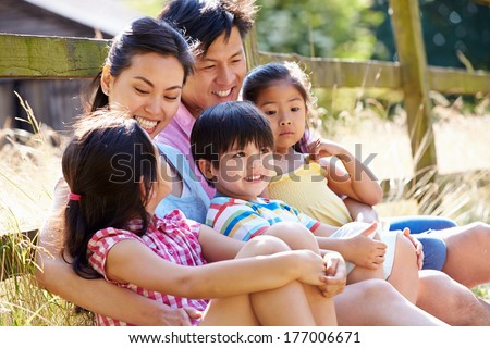 Asian Family Relaxing By Gate On Walk In Countryside - stock photo