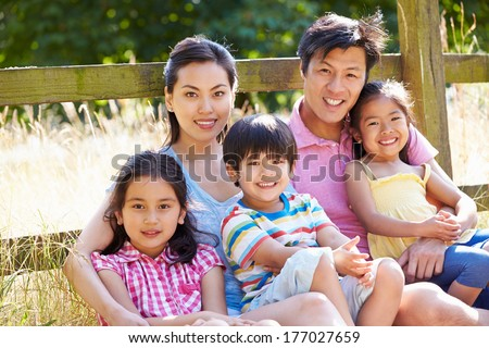 Asian Family Relaxing By Gate On Walk In Countryside