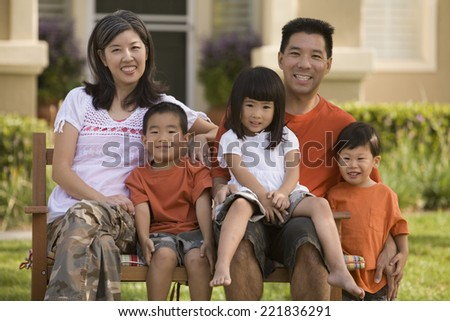 Asian family sitting on bench