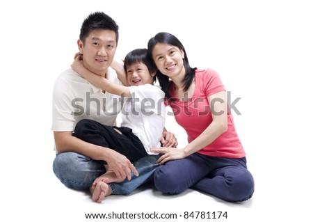 asian family sitting on floor - stock photo