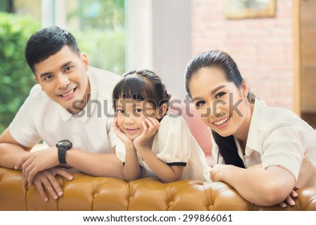 Asian family Sitting on sofa and smiling - stock photo