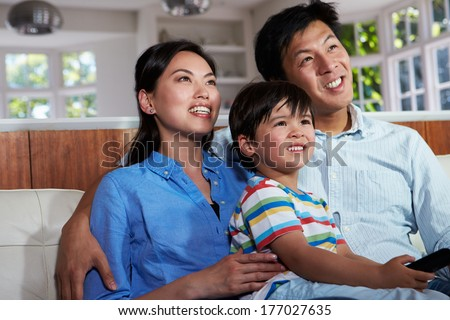 Asian Family Sitting On Sofa Watching TV Together - stock photo