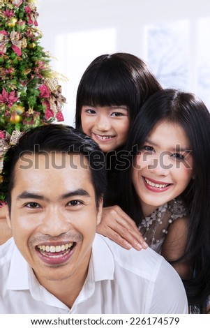 Asian family smiling on camera at home with christmas tree background - stock photo
