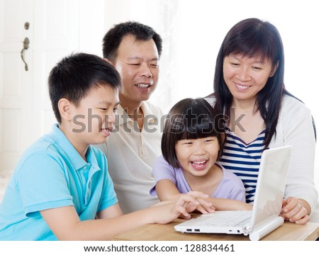 Asian family using laptop - stock photo