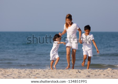 Asian family walk together on tropical beach - stock photo