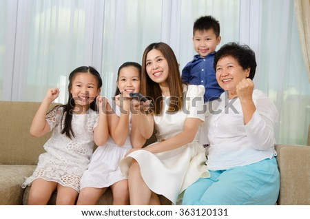 Asian family watching television and shouting on their home side in a sporting competition - stock photo
