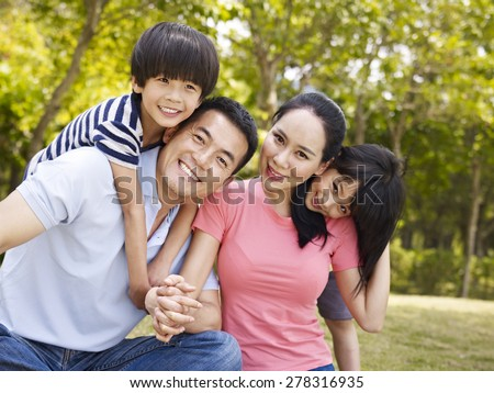 asian family with two children taking a family photo outdoors in a city park. - stock photo