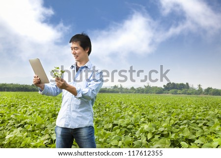 asian farmer with tablet pc - stock photo