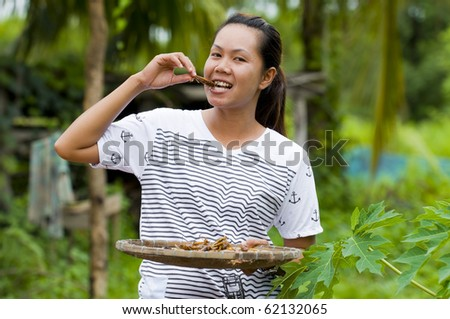 asian farmer woman eating fried grasshoppers - stock photo