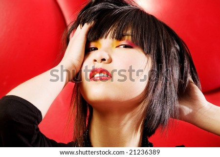 Asian fashion model on bright red background