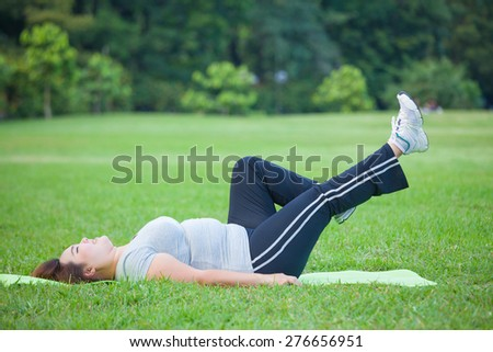Asian fat woman lying by exercise leg upwards at the park - stock photo