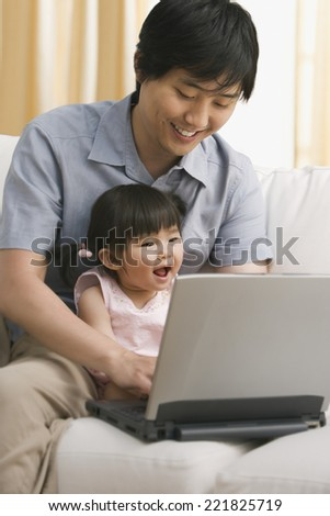 Asian father and baby daughter looking at laptop - stock photo