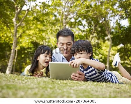 asian father and children lying on grass looking at tablet computer in a park. - stock photo