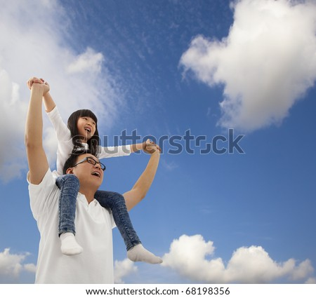 Asian father and daughter under blue sky - stock photo