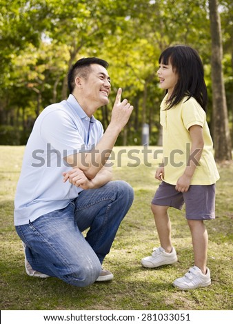 asian father and elementary-age daughter enjoying a conversation in park. - stock photo