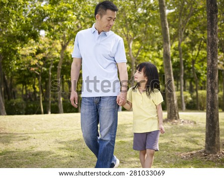 asian father and elementary-age daughter enjoying a walk in nature. - stock photo