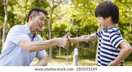 asian father and elementary-age son sealing a deal or promise outdoors in a park. - stock photo