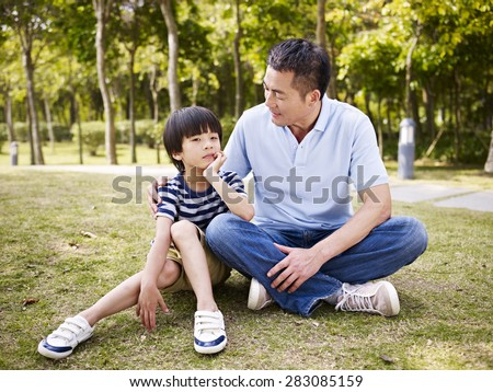 asian father and elementary-age son sitting on grass outdoors having a conversation. - stock photo
