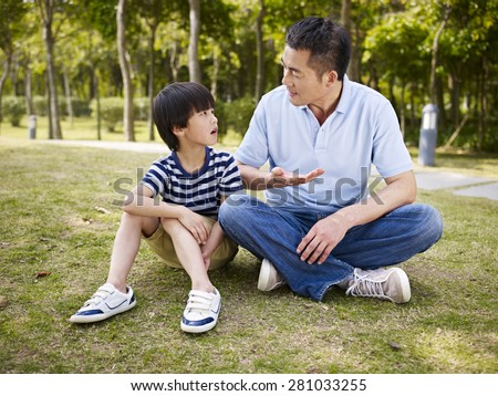 asian father and elementary-age son sitting on grass outdoors having a serious conversation. - stock photo