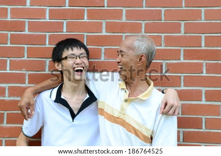 Asian father and son laugh happily - stock photo