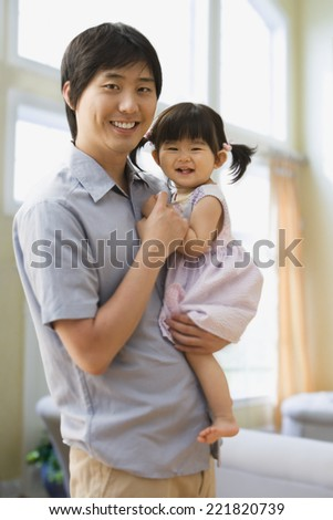 Asian father holding baby daughter - stock photo