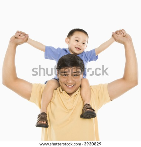 Asian father holding son on shoulders smiling in front of white background.