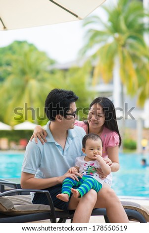 asian father , mother and daughter having holiday on a pool - stock photo