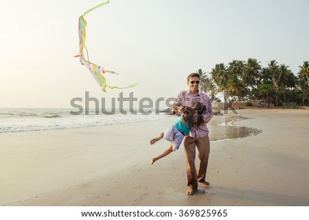 Asian father playing active outdoor games with his daughter on the bech. Happy mixed race family having fun on the beach at sunset.  - stock photo