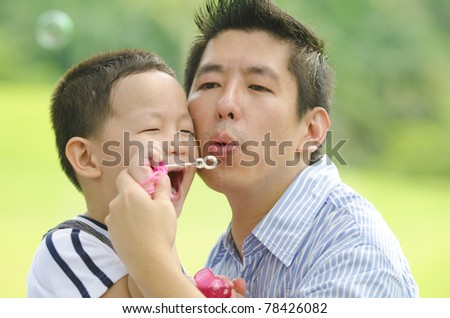asian father playing with child with soap bubble
