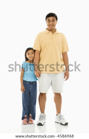 Asian father standing holding hands with daughter. - stock photo