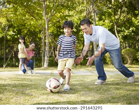 asian father teaching son to play soccer (football) in a park while mother and daughter watching from behind. - stock photo