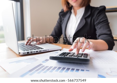 Asian female accountant or banker making calculations. Savings, finances and economy concept.