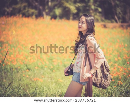 Asian female backpacker with camera - stock photo