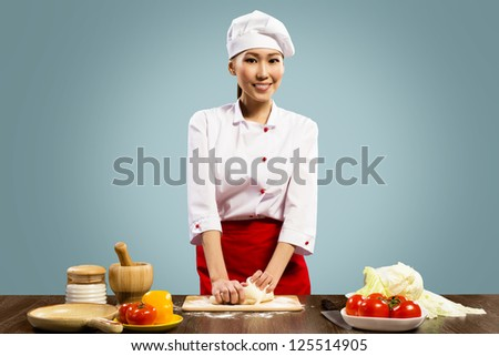 Asian female chef cooking pizza dough, looks at the camera and smiling