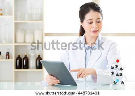 asian female chemist use notepad to research for future Chemical formula and holding molecular model - stock photo
