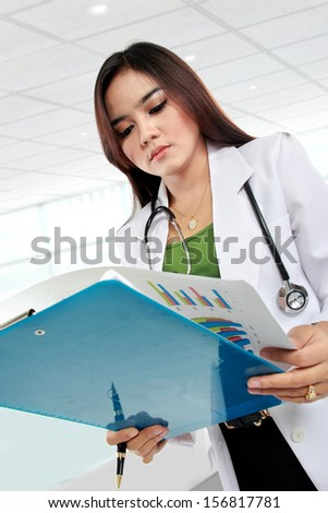 Asian female doctor working with clipboard in hospital