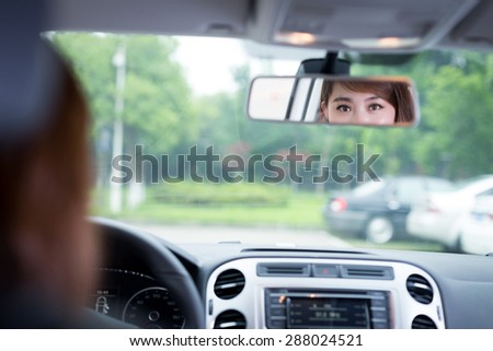 asian female driver touching dashboard in car - stock photo