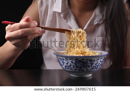 Asian female holing noodles using chopsticks with focus on noodles