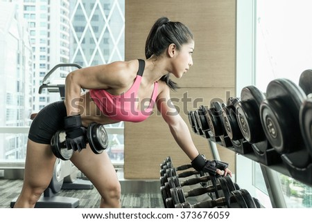 Asian female in sports clothing workout on grey background. Muscular female body with dumbbells in gym.