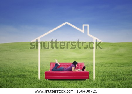 Asian female is working on laptop while lying on sofa with house picture - stock photo