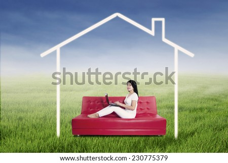 Asian female is working on laptop while sitting on sofa with house picture - stock photo