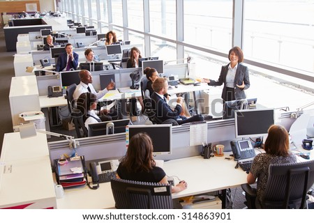 Asian female manager addressing workers in open plan office - stock photo