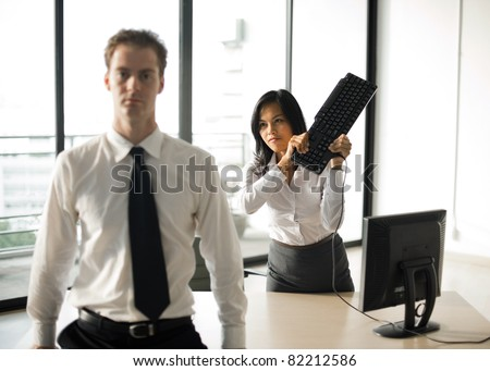Asian female office subordinate employee violently swinging a keyboard hitting her bad Caucasian British male boss over the head in anger, frustration, demonstrating workplace violence. Horizontal