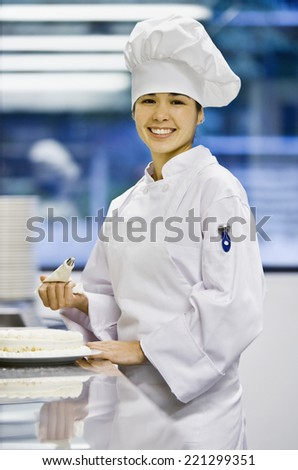 Asian female pastry chef holding piping bag - stock photo