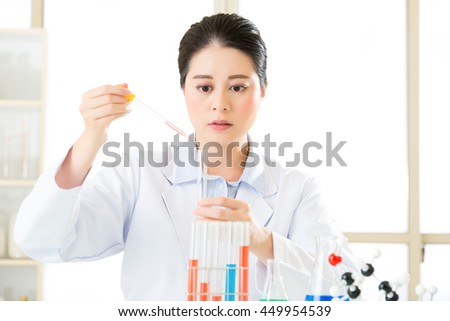 asian female scientist Breaking scientific boundaries with her research use dropper in Laboratory - stock photo